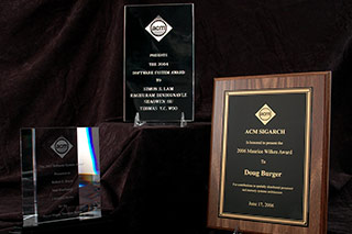 Photo of three different style awards, one made of metal and wood, and two on etched glass.